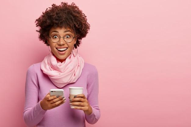 아프로 헤어 스타일로 꽤 젊은 어두운 피부를 가진 여자, 휴대 전화와 일회용 커피 한잔, 보라색 폴로 넥과 스카프를 입고 분홍색 벽 위에 포즈를 취합니다. 커뮤니케이션, 라이프 스타일, 기술 무료 사진
