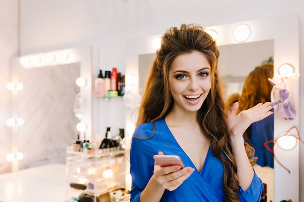 Pretty young excited joyful woman in blue shirt with long brunette hair expressing positive emotions to camera in beauty salon Free Photo