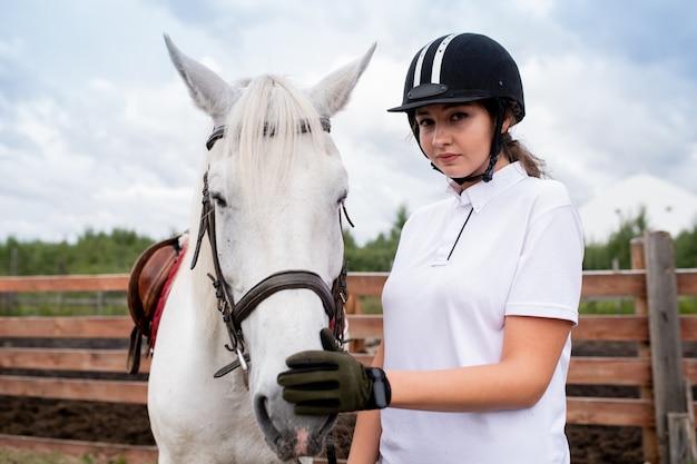 Довольно молодая женщина в конном шлеме и перчатках трогает нос белого скакового коня во время тренировки Premium Фотографии