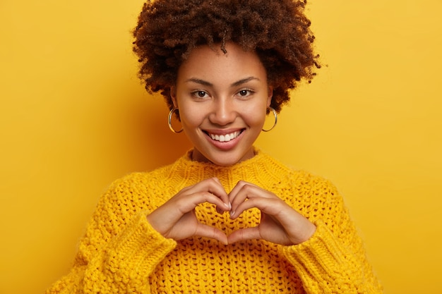 Pretty young female makes love gesture, confesses and expresses truthful feelings, smiles broadly, shows white even teeth, wears yellow sweater, has tender look Free Photo