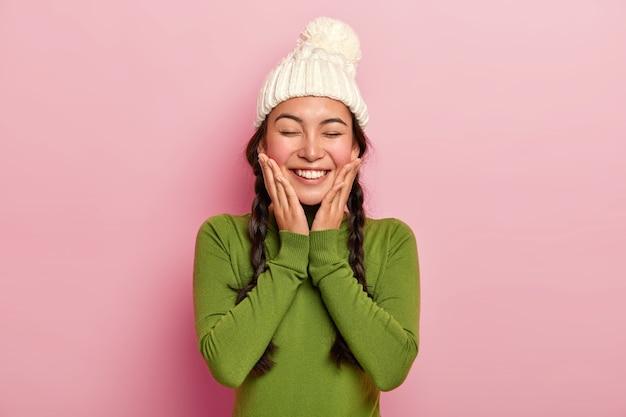 Modello femminile abbastanza giovane si sente piacere, tocca le guance con entrambi i palmi, indossa un cappello bianco caldo invernale e dolcevita verde casual, ha un ampio sorriso splendente, posa sul muro rosa Foto Gratuite