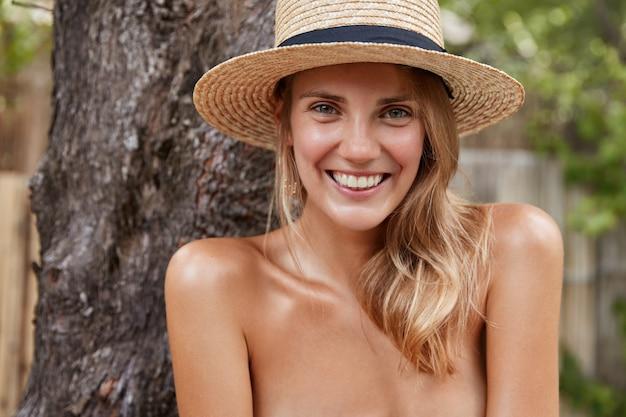 裸の体と健康な純粋な肌を持つかなり若い女性モデルは、トロピカルラグーンで自由な時間を過ごし、夏の帽子をかぶって、良い休息に満足しています。美しさと幸福の概念 無料写真