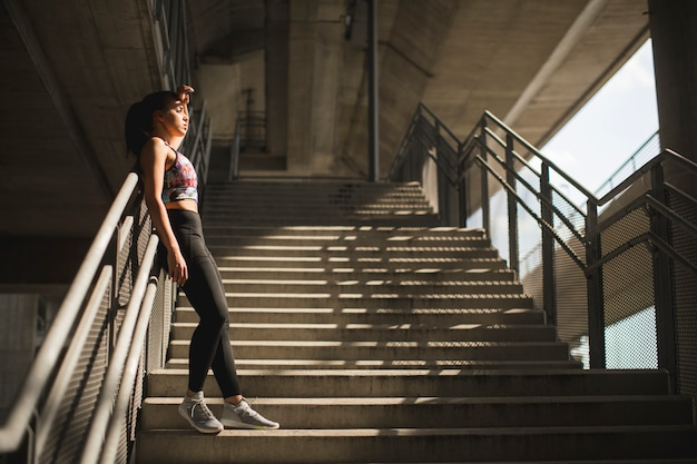 Pretty young female runner resting on stairs Premium Photo
