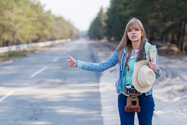 Pretty young female tourist hitchhiking along a road Free Photo