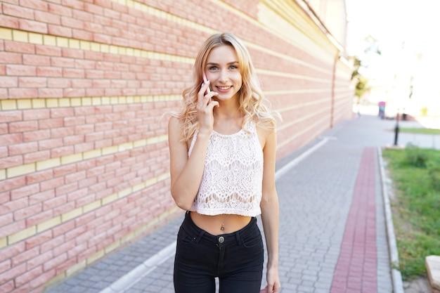 Довольно молодая женщина с помощью белого мобильного телефона дома улыбается Premium Фотографии
