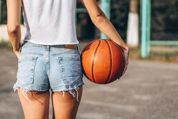 Pretty young girl holding basketball ball, rear view. Premium Photo