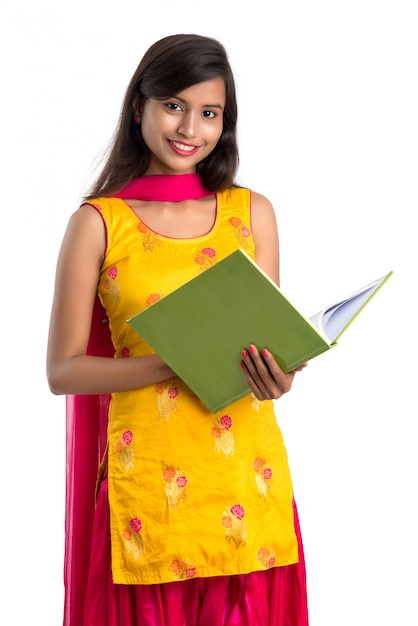 Pretty young girl holding book and posing on white surface Premium Photo