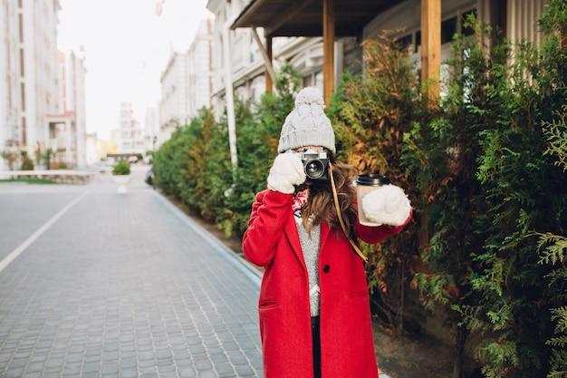 赤いコートとニットの帽子が通りを歩いてかなり若い女の子。彼女は手にコーヒーの写真を作ります。 無料写真