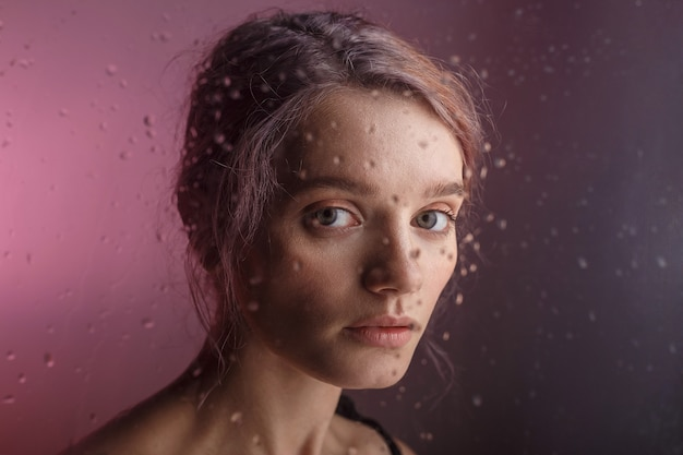 Pretty young girl looks into camera on purple background. blurry drops of water run down the glass in front of her face Premium Photo