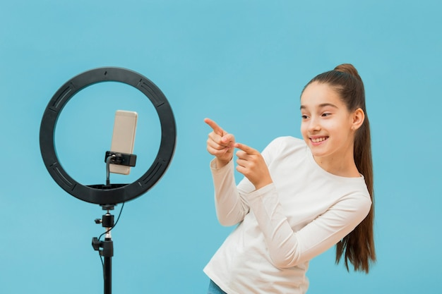 Pretty young girl recording video Free Photo
