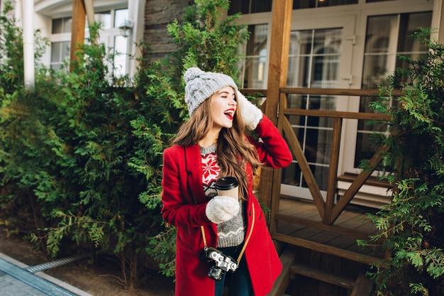 赤いコートの長い髪と木造住宅のニット帽子のかなり若い女の子。彼女はコーヒーを手に持って、白い手袋をし、横に表現します。 無料写真