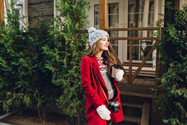 赤いコートと木造住宅の通りを歩いてニット帽子の長い髪を持つかなり若い女の子。彼女はカメラを持っており、白い手袋で行くためにコーヒーを持っています。 無料写真