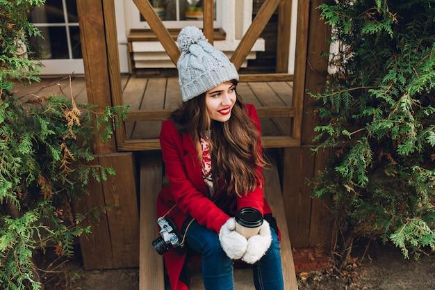 屋外の緑の枝の間の木製の階段の上に座って赤いコートに長い髪のかなり若い女の子。彼女は灰色のニットの帽子を持っており、白い手袋でコーヒーを抱え、横に笑顔を見せています。 無料写真