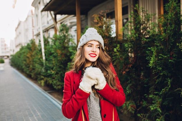 Pretty young girl with long hair in red coat and knitted hat walking on wooden house  . she holds coffee to go in white gloves, smiling friendly to side. Free Photo