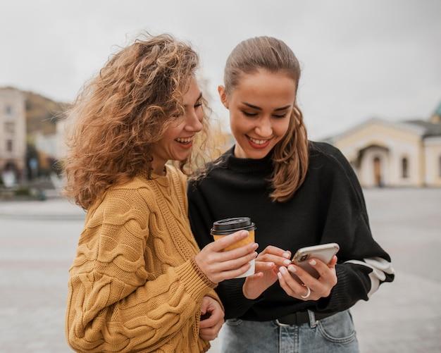 Ragazze abbastanza giovani che controllano insieme un telefono Foto Gratuite