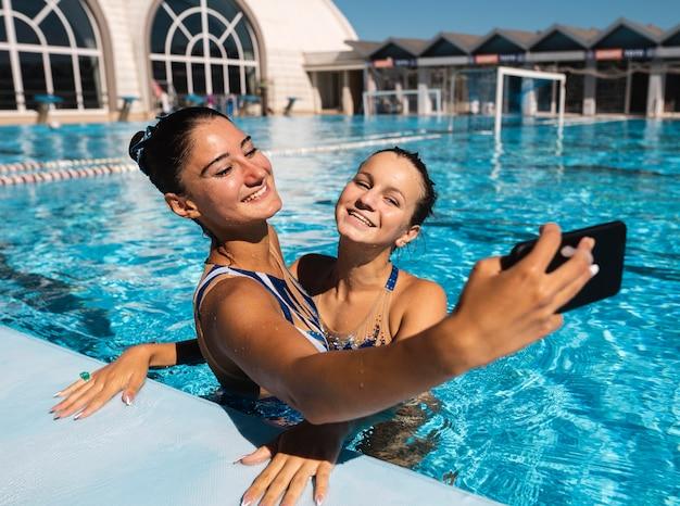 Belle ragazze giovani che prendono un selfie in piscina Foto Gratuite