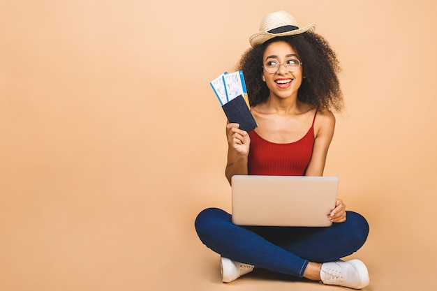 Pretty young happy black woman sitting on the floor with laptop and plane tickets over beige. Premium Photo