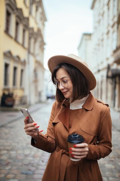 Довольно молодая леди разговаривает по мобильному телефону, прогулки на свежем воздухе в холодный осенний день Бесплатные Фотографии