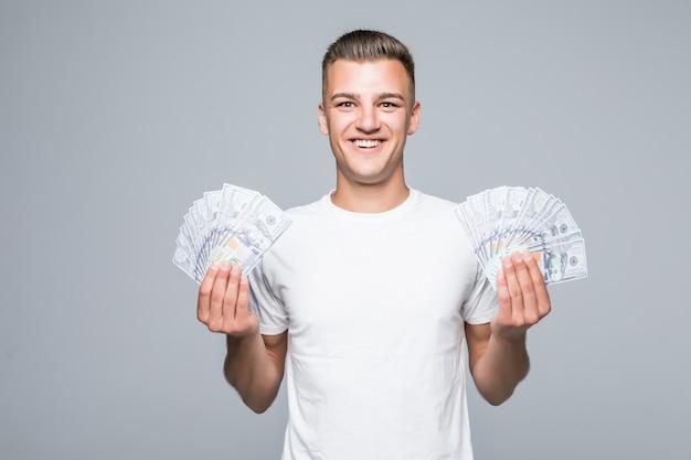 Довольно молодой человек в белой футболке держит в руках много долларовых купюр, изолированные на белом фоне Бесплатные Фотографии