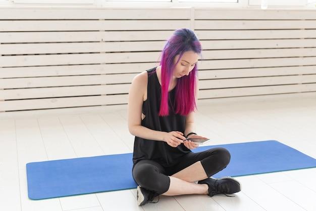 Симпатичная молодая девушка смешанной расы с фиолетовыми волосами подсчитывает сожженные калории с помощью приложения на своем смартфоне, сидя на спортивном коврике в тренажерном зале. концепция йоги и фитнеса. Premium Фотографии