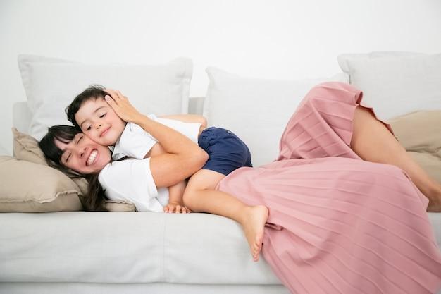 ソファの上に横たわるとかわいい息子を愛で抱きしめるかなり若いお母さん。 無料写真