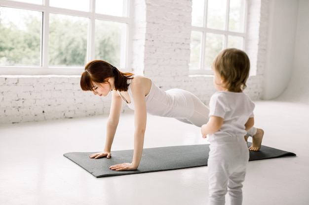 꽤 젊은 어머니는 큰 가벼운 체육관에서 작은 아기와 함께 체중 감량을위한 판자를하고, 요가를하고 적합하고 재생 프리미엄 사진
