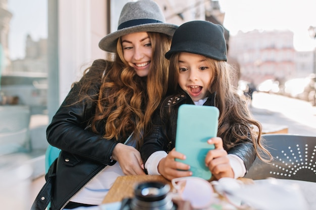 Pretty young mother and her cute daughter having fun and  take selfies. little girl surprised looking in phone and smile on the sunny city background. stylish family, true emotion, good mood. Free Photo