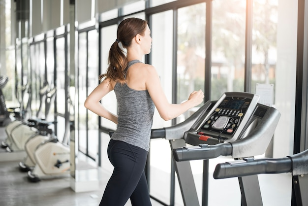 Pretty young sport woman is running on treadmill in gym, healthy lifestyle Premium Photo