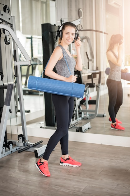 Pretty young sport woman is workout with mat  in gym Premium Photo