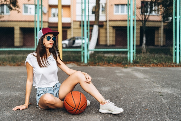 Pretty young sporty girl with basketball ball outdoor. Premium Photo