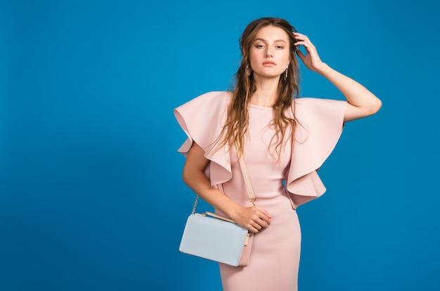 핑크 럭셔리 드레스, 여름 패션 트렌드, 세련된 스타일, 블루 스튜디오 배경, 유행 핸드백을 들고 꽤 젊은 세련된 섹시한 여자 무료 사진