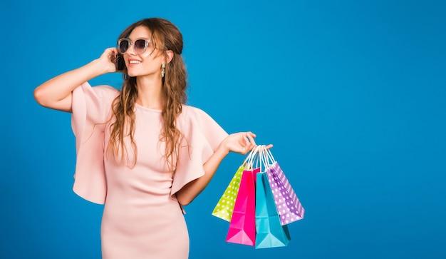 Piuttosto giovane donna sexy elegante in abito di lusso rosa, tendenza moda estiva, stile chic, occhiali da sole, sfondo blu studio, shopping, con sacchetti di carta, parlando al cellulare, maniaco dello shopping Foto Gratuite