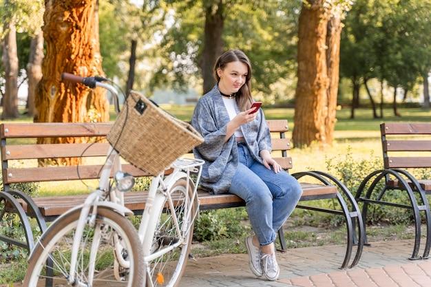 Довольно молодая женщина просматривает мобильный телефон Бесплатные Фотографии