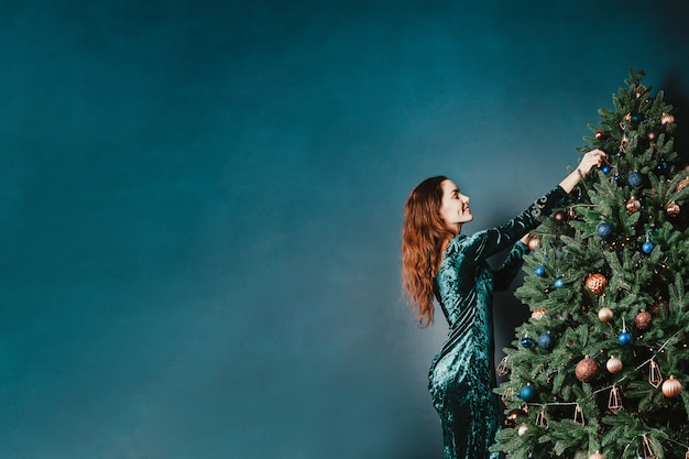 Pretty young woman decorating christmas tree Premium Photo
