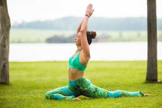 Довольно молодая женщина делает упражнения йоги в парке Бесплатные Фотографии