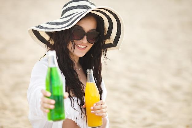 ビーチでカクテルを飲んでかなり若い女性。ドリンクを提供している魅力的な女の子。レモネードを飲む美しい女性 Premium写真