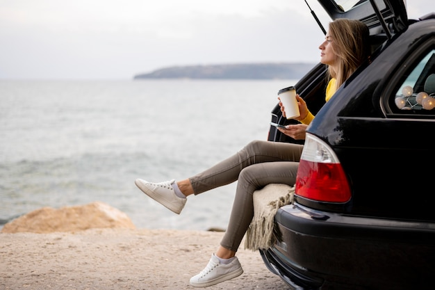 Pretty young woman enjoying road trip Free Photo