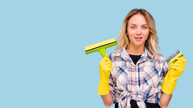 Pretty young woman holding cleaning supplies against blue background Free Photo