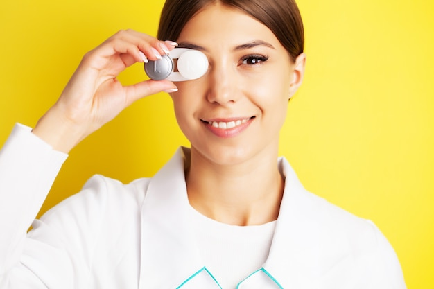 Pretty young woman holding a container with contact lenses for eyesight Premium Photo