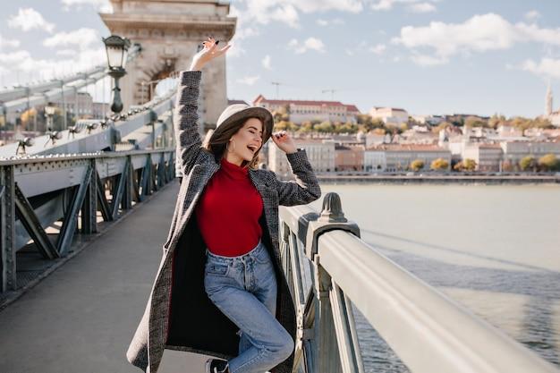 Довольно молодая женщина в синих джинсах и длинном пальто танцует на мосту возле триумфальной арки Бесплатные Фотографии