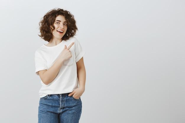 カジュアルな服を着てかなり若い女性の指の右上隅を指して、チェックアウト製品を招待 無料写真