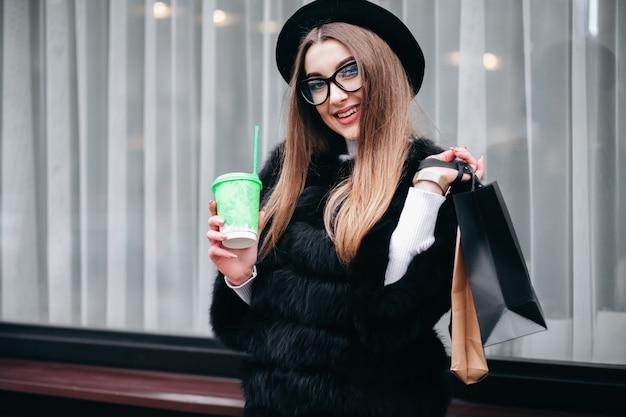 안경에 꽤 젊은 여자는 긴 쇼핑 후 그녀의 손에 커피 한잔과 함께 도시 주위를 걷고있다 프리미엄 사진
