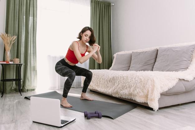 Довольно молодая женщина в спортивной одежде смотрит онлайн-видео на ноутбуке и делает фитнес-упражнения Premium Фотографии
