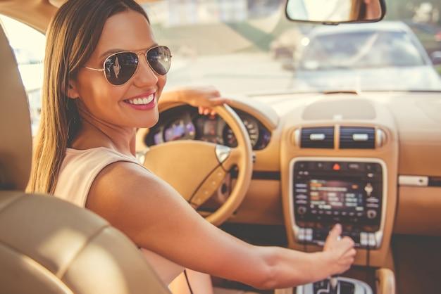 Довольно молодая женщина в солнцезащитных очках смотрит на камеру. Premium Фотографии