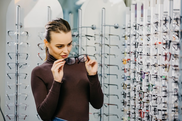 Pretty young woman is choosing new glasses at optical store. Premium Photo
