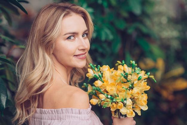美しい黄色の花を保持しているカメラを見てかなり若い女性 無料写真