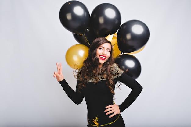 Довольно молодая женщина на белом пространстве держит золотые и черные шары. удивительная девушка с длинными вьющимися волосами, в черном элегантном платье Бесплатные Фотографии