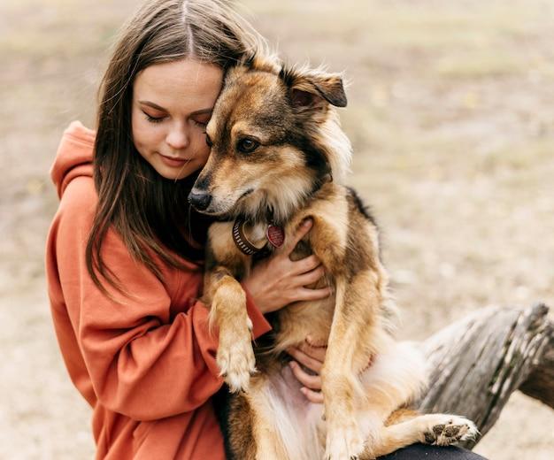 Довольно молодая женщина гладит свою собаку Premium Фотографии