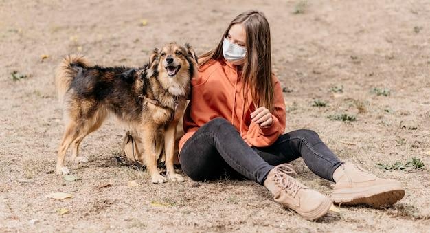 Donna abbastanza giovane che accarezza il suo cane Foto Gratuite