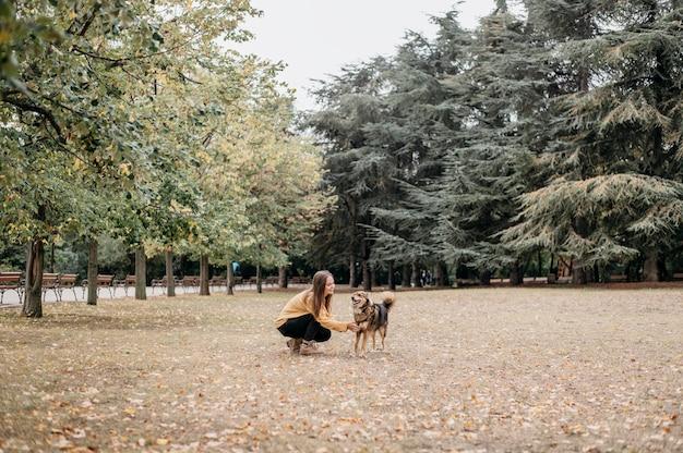 Довольно молодая женщина гладит свою собаку Бесплатные Фотографии